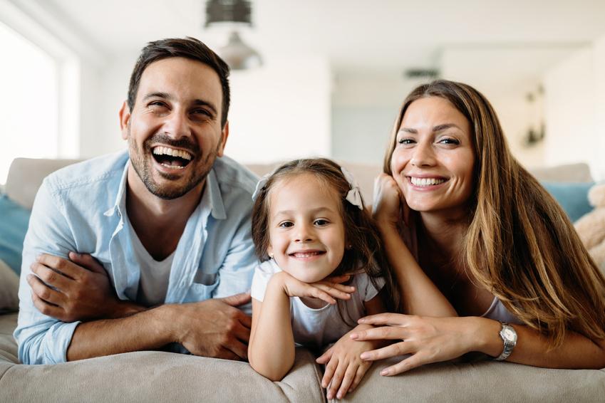 Privathaftpflicht: Eine junge Familie freut sich und liegt auf dem Sofa